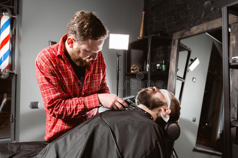 Barber work with clipper machine in barbershop. Professional trimmer tool cuts beard and hair of young guy in barber. Shop salon royalty free stock images