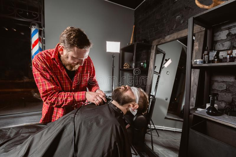 Beard cutting, face care. Barber work with clipper machine in barbershop. Professional trimmer tool cuts beard and hair. Barber work with clipper machine in stock image