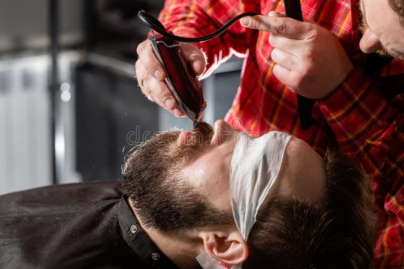 Beard cutting, face care. Barber work with clipper machine in barbershop. Professional trimmer tool cuts beard and hair. Barber work with clipper machine in stock photography