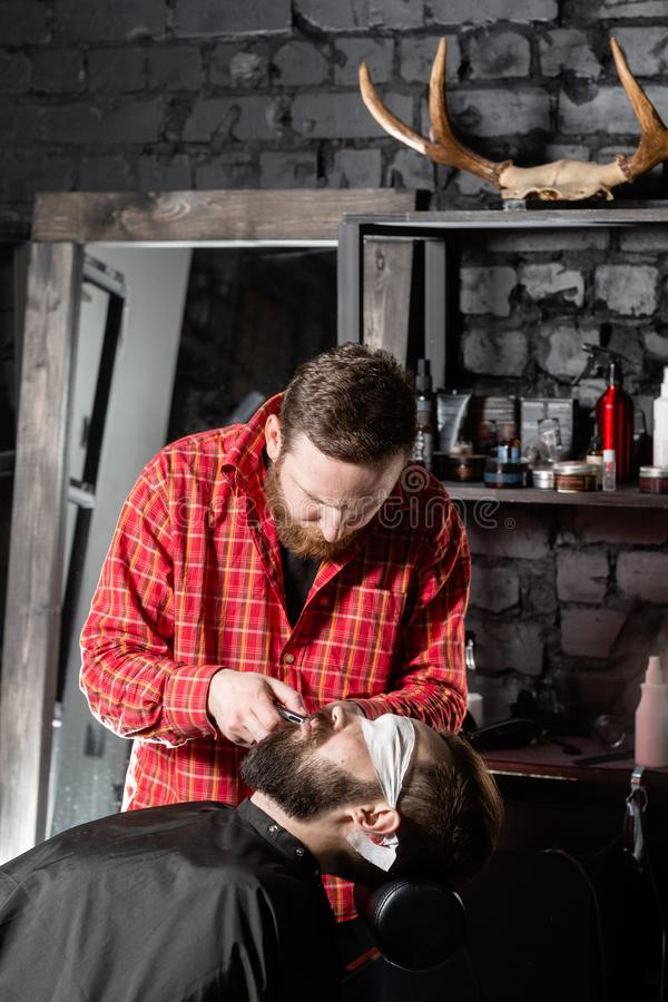 Beard cutting, face care. Barber work with clipper machine in barbershop. Professional trimmer tool cuts beard and hair. Barber work with clipper machine in royalty free stock photography