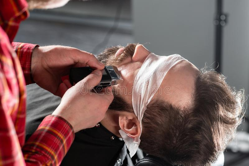 Beard cutting, face care. Barber work with clipper machine in barbershop. Professional trimmer tool cuts beard and hair stock image