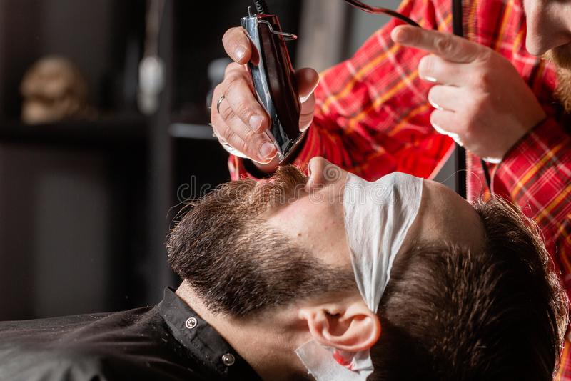 Beard cutting, face care. Barber work with clipper machine in barbershop. Professional trimmer tool cuts beard and hair stock photos