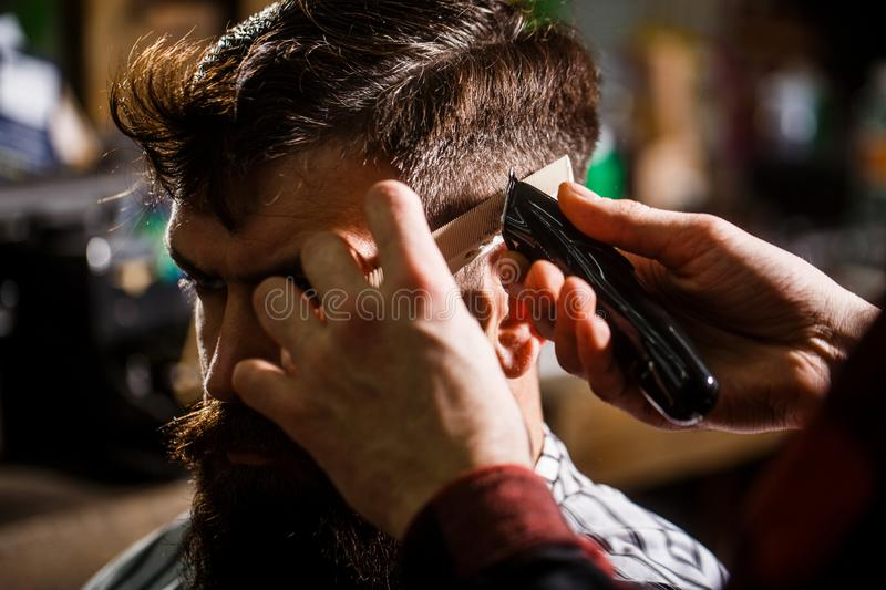 Barber works with hair clipper. Hipster client getting haircut. Hands of barber with hair clipper, close up. Bearded man royalty free stock image