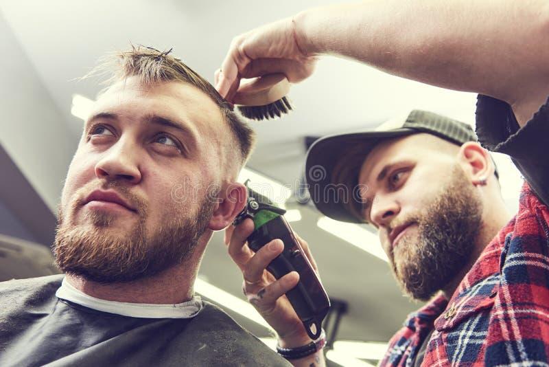 Barberare- eller hårstylist på arbete Bitande hår för frisör av klienten royaltyfria bilder