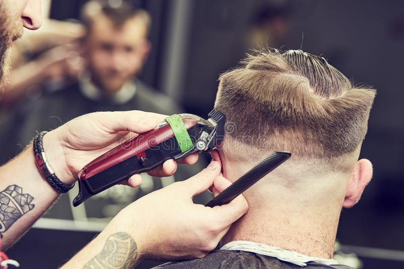 Barberare- eller hårstylist på arbete Bitande hår för frisör av klienten fotografering för bildbyråer
