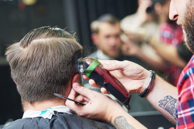 Barberare- eller hårstylist på arbete Bitande hår för frisör av klienten arkivfoto