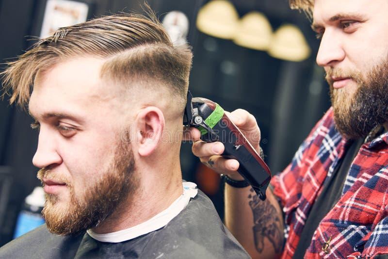 Barberare- eller hårstylist på arbete Bitande hår för frisör av klienten royaltyfri fotografi