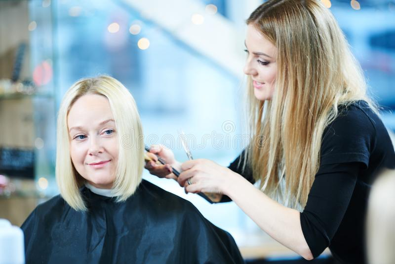 Barberare eller stylist på arbete Bitande kvinnahår för frisör royaltyfri fotografi