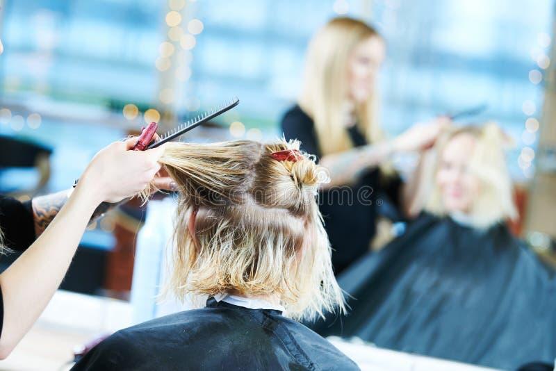 Barberare eller stylist på arbete Bitande kvinnahår för frisör arkivbilder