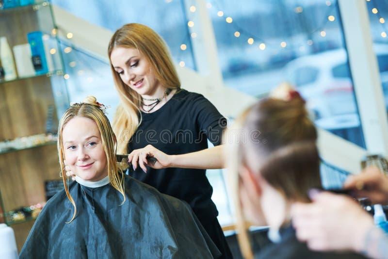 Barberare eller stylist på arbete Bitande kvinnahår för frisör royaltyfria foton