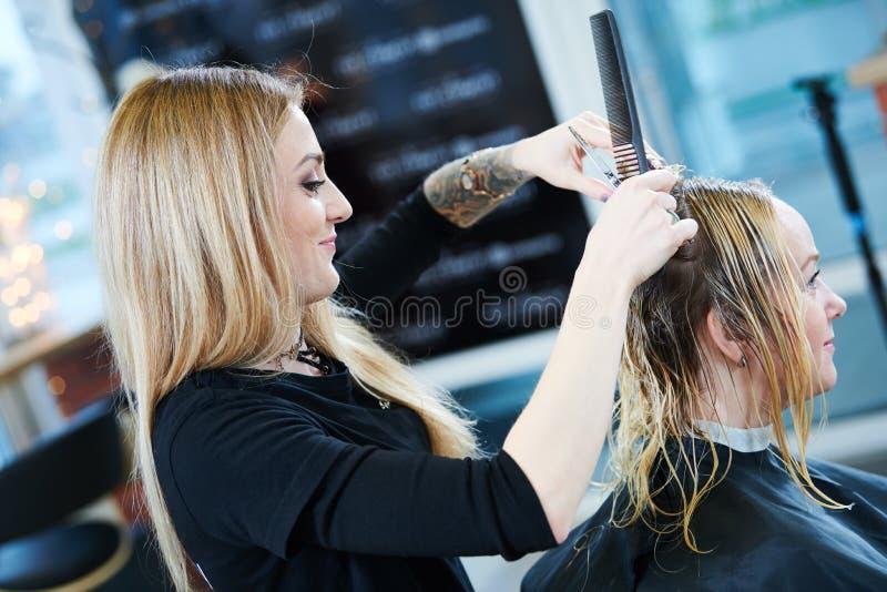 Barberare eller stylist på arbete Bitande kvinnahår för frisör royaltyfri foto