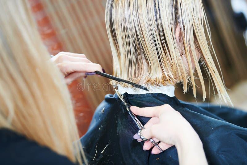 Barberare eller stylist på arbete Bitande kvinnahår för frisör arkivbild