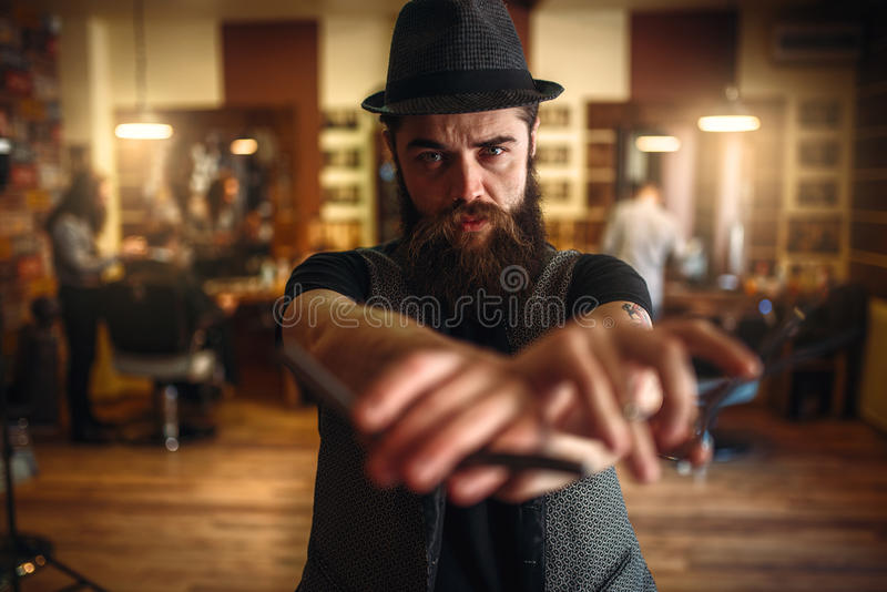 Barberare i hållande sax för hatt och rak rakkniv royaltyfria bilder
