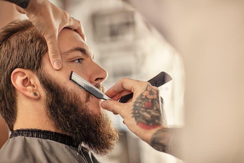 Barberare med den gammalmodiga svarta rakkniven arkivbild