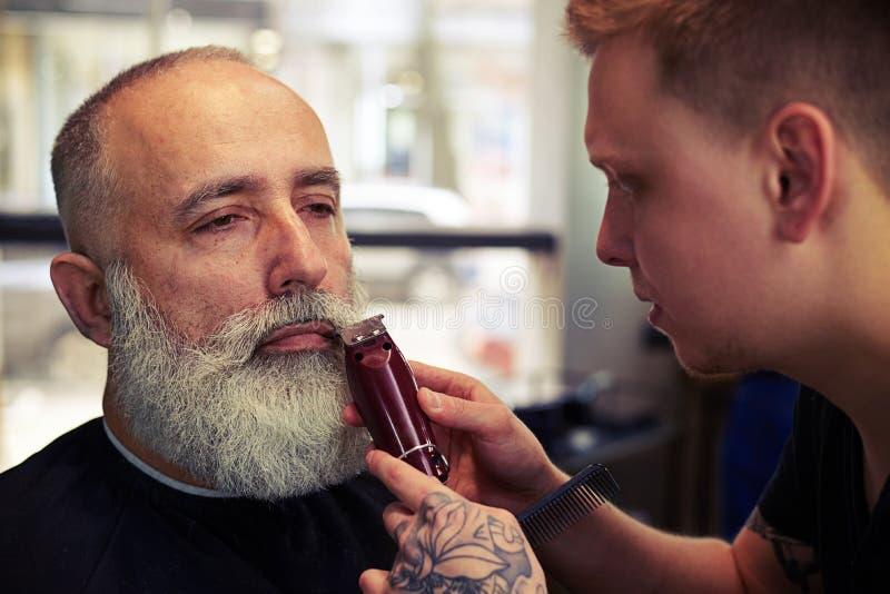 Barberare med tatueringdanandefrisyr till den höga mannen för hipster royaltyfri bild
