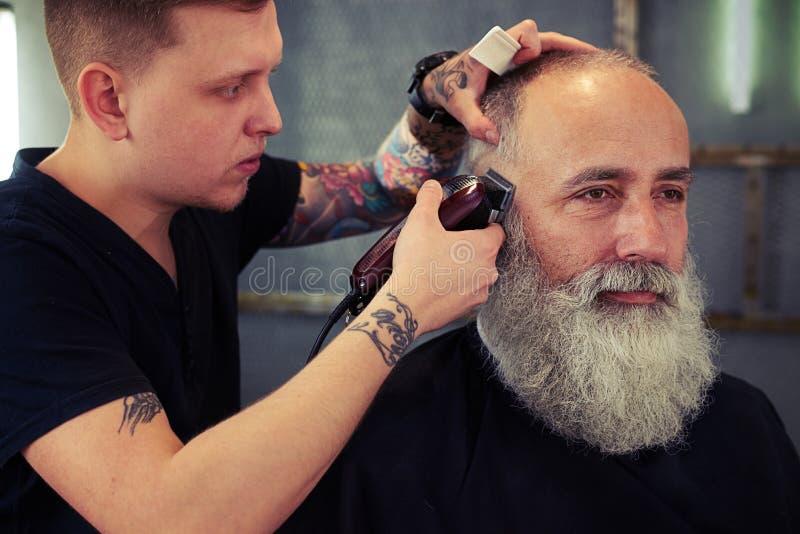 Barberare med tatueringdanandefrisyr till den höga mannen för stilig hipster fotografering för bildbyråer