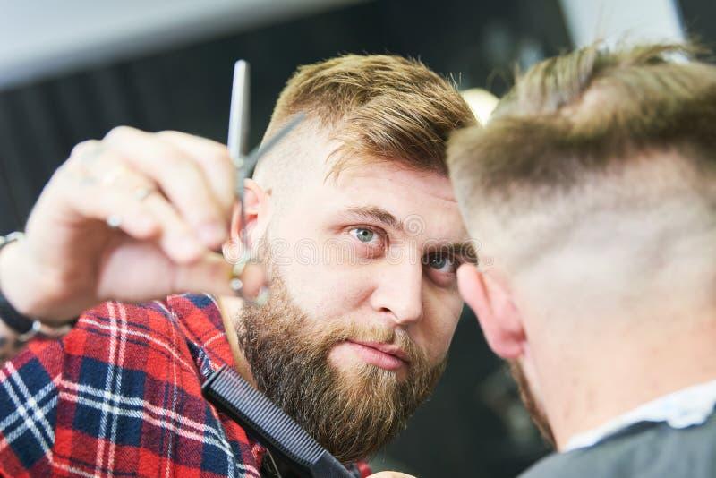 Barberare p? arbete Bitande h?r f?r fris?r av klienten arkivbild