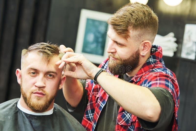 Barberare p? arbete Bitande h?r f?r fris?r av klienten royaltyfri fotografi