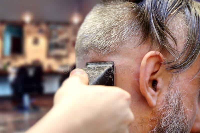 Barberare som gör en frisyr genom att använda beskärareklippmaskinen arkivfoto