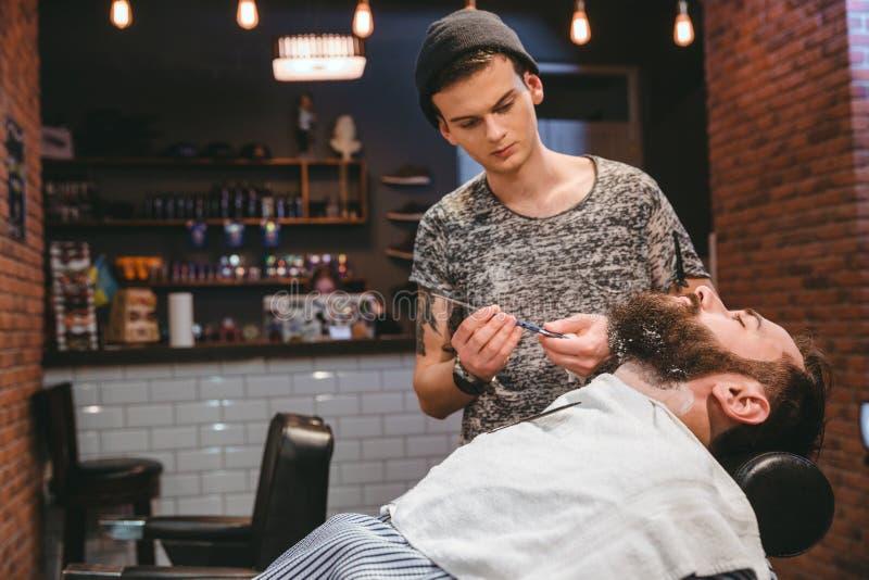 Barberare som rakar den skäggiga mannen med den raka rakkniven royaltyfri foto