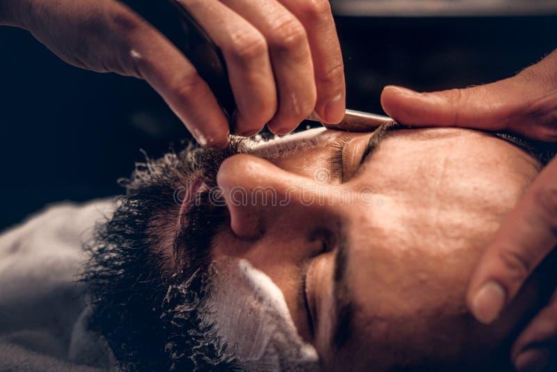 Barberare som rakar den skäggiga mannen med en skarp rakkniv arkivfoto