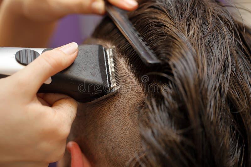 Barberare som rakar hår vid den elektriska beskäraren royaltyfri foto