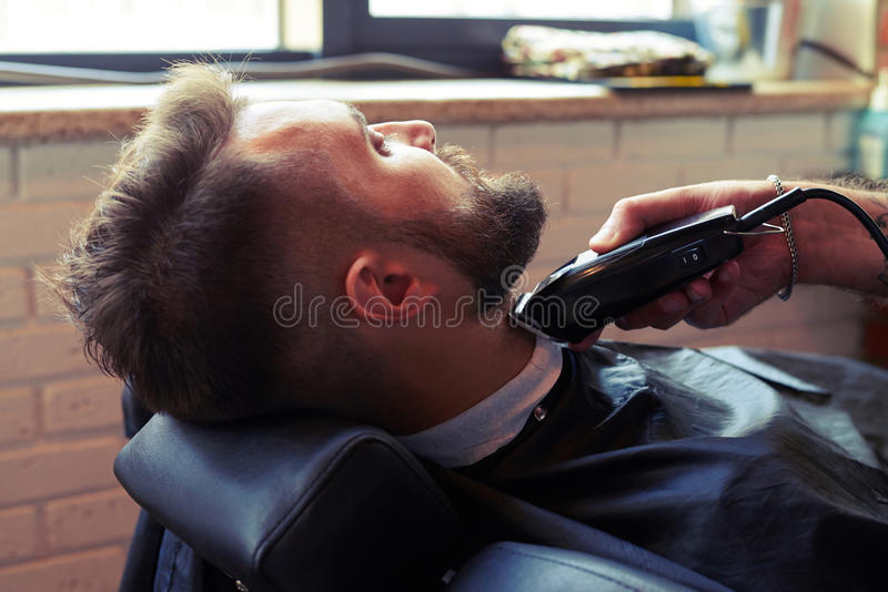 barberare som rakar skägget med rakapparaten arkivfoto