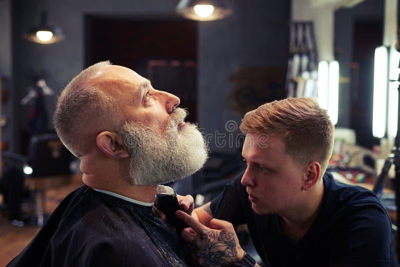 Barberaredanandefrisyr till den stiliga attraktiva höga mannen arkivfoton