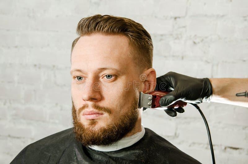 Barberarehanden i handskar klippte h?r och mannen f?r vuxen gihger f?r rakningar den sk?ggiga p? en bakgrund f?r tegelstenv?gg N? royaltyfria bilder