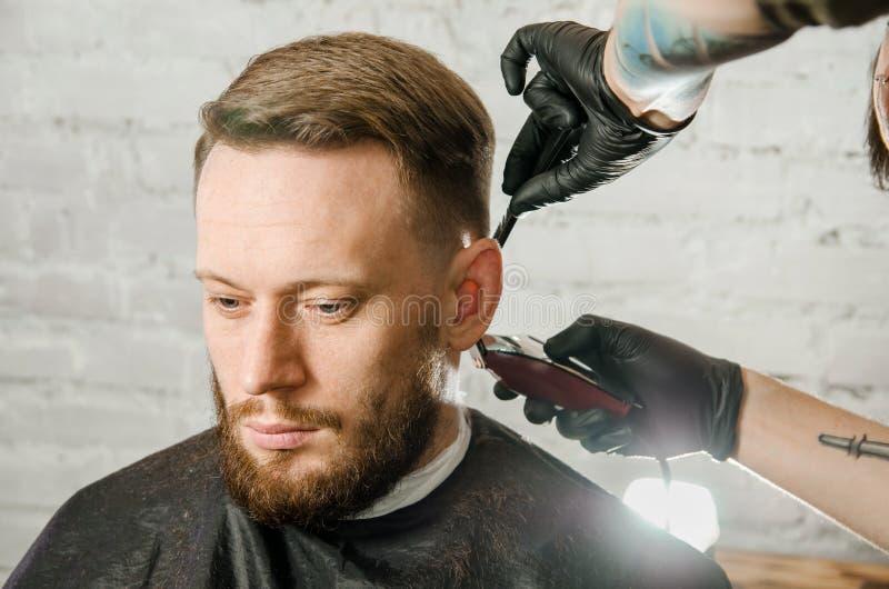 Barberarehanden i handskar klippte h?r och mannen f?r vuxen gihger f?r rakningar den sk?ggiga p? en bakgrund f?r tegelstenv?gg N? royaltyfri bild