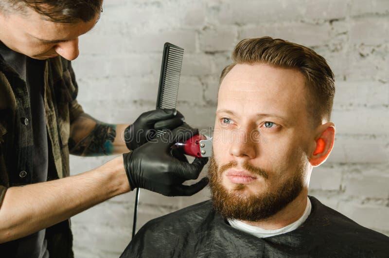 Barberarehanden i handskar klippte h?r och mannen f?r vuxen gihger f?r rakningar den sk?ggiga p? en bakgrund f?r tegelstenv?gg N? arkivfoton