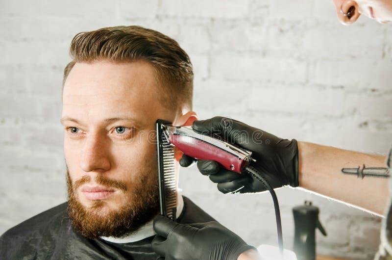 Barberarehanden i handskar klippte h?r och mannen f?r vuxen gihger f?r rakningar den sk?ggiga p? en bakgrund f?r tegelstenv?gg N? arkivbild