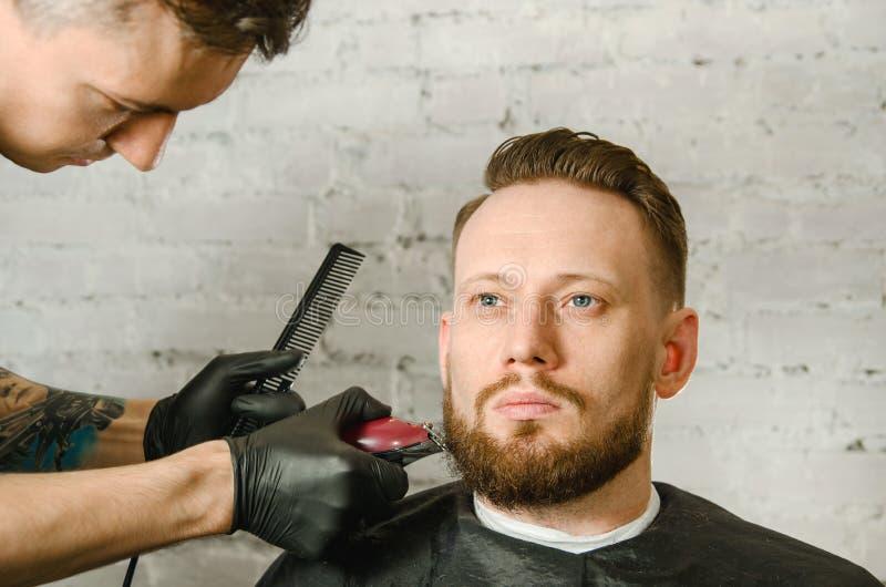 Barberarehanden i handskar klippte h?r och mannen f?r vuxen gihger f?r rakningar den sk?ggiga p? en bakgrund f?r tegelstenv?gg N? fotografering för bildbyråer