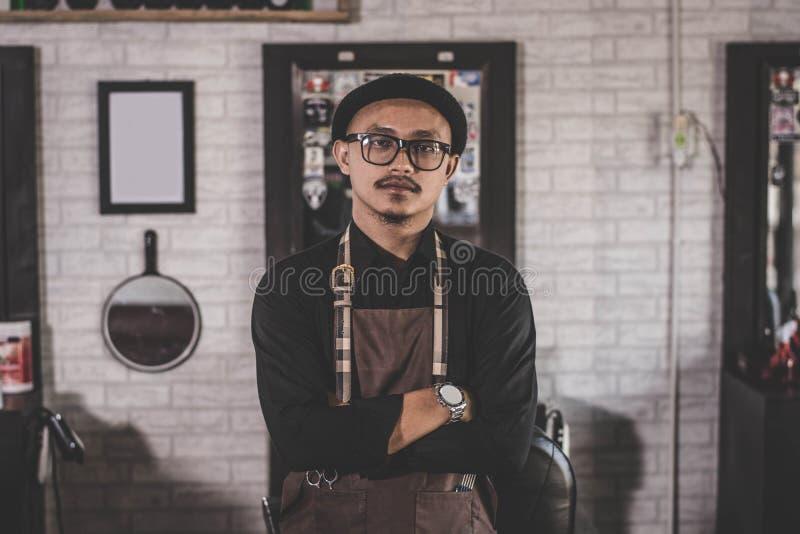 Barberaremanfrisör som poserar och står på frisersalongsalongen royaltyfria bilder