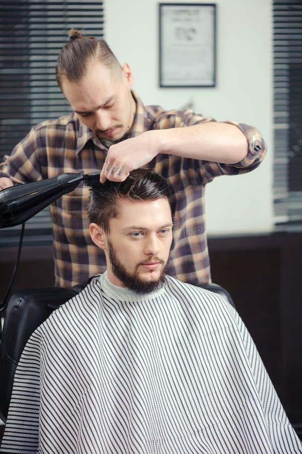 Barberaren gör en frisyr arkivfoto