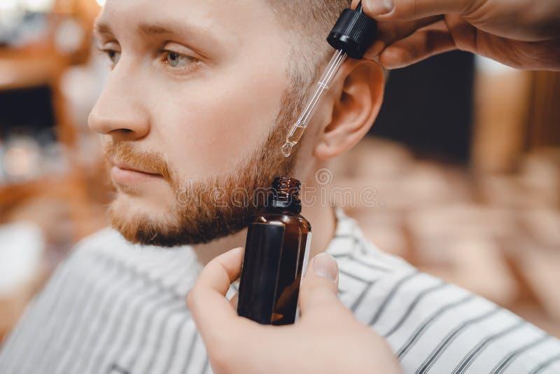 Barberaren gör olja för omsorg och tillväxt av skägget, frisersalong arkivfoto