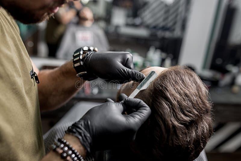Barberaren i svarta handskar klipper templet av den brutala skäggiga unga mannen med en rak rakkniv på en frisersalong royaltyfri fotografi