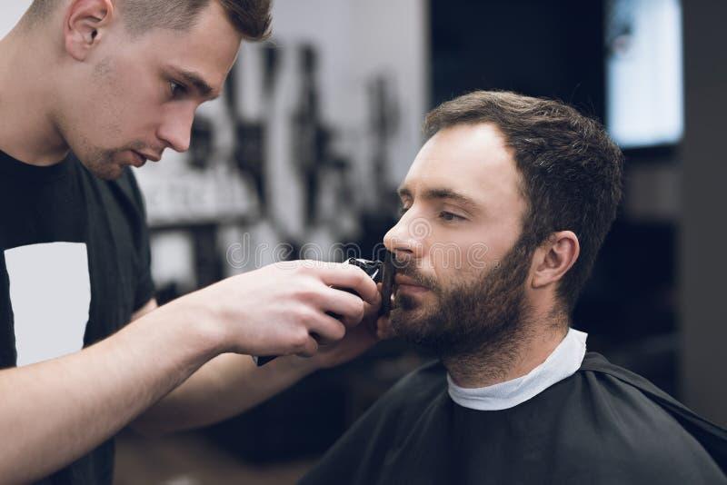 Barberaren klipper ett skägg till en man i en hårsalong fotografering för bildbyråer
