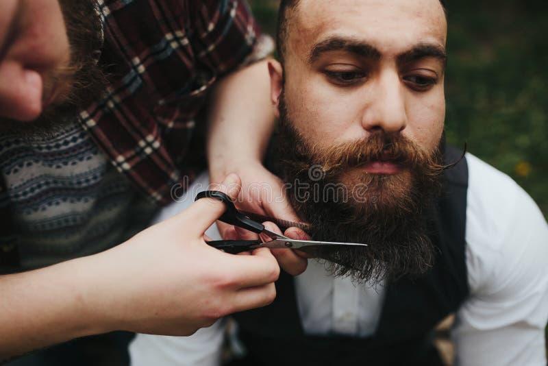 Barberaren rakar en skäggig man arkivfoton