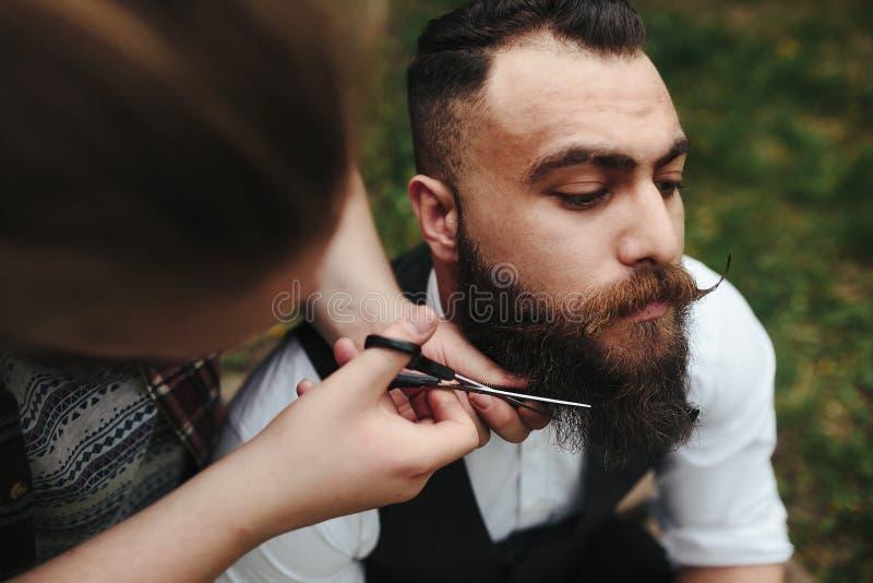 Barberaren rakar en skäggig man royaltyfri bild