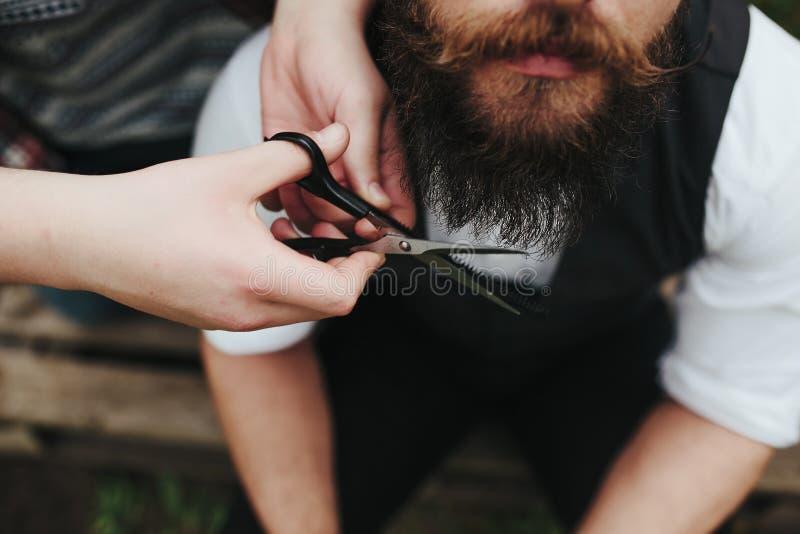 Barberaren rakar en skäggig man fotografering för bildbyråer