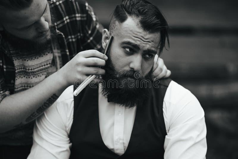 Barberaren rakar en skäggig man arkivfoto