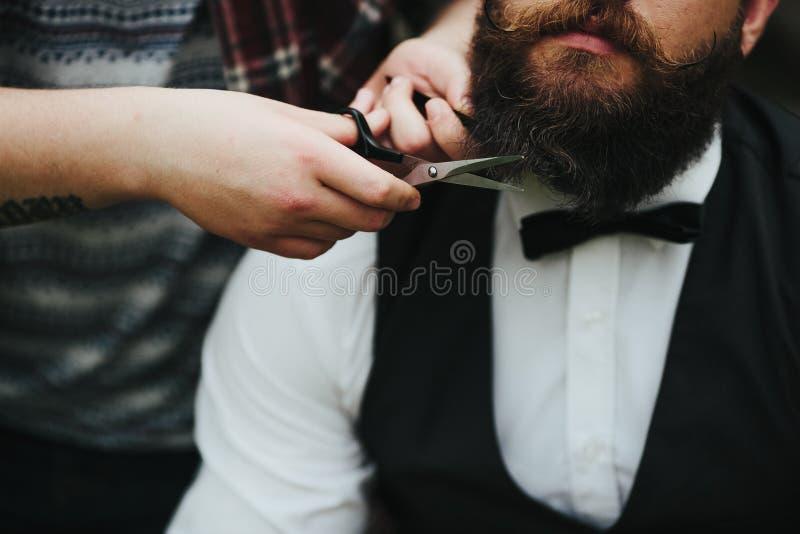 Barberaren rakar en skäggig man royaltyfri foto