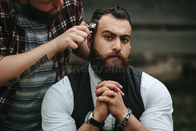 Barberaren rakar en skäggig man arkivbild