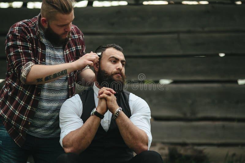 Barberaren rakar en skäggig man royaltyfri fotografi