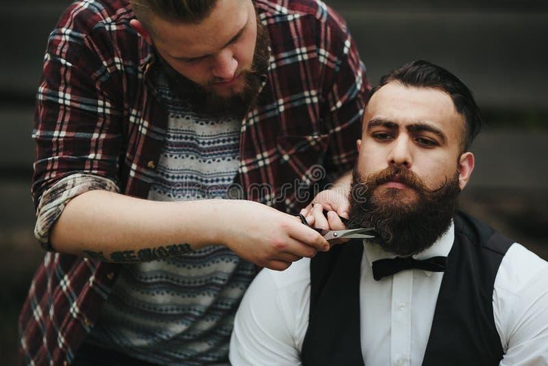 Barberaren rakar en skäggig man utomhus royaltyfria foton