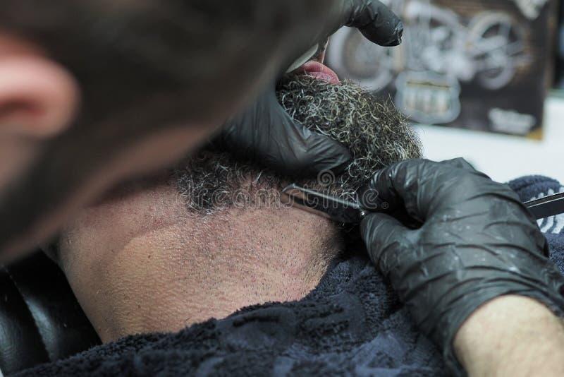 Barberaren rakar skägget av en äldre man med den skarpa rakkniven för grått hår arkivfoton