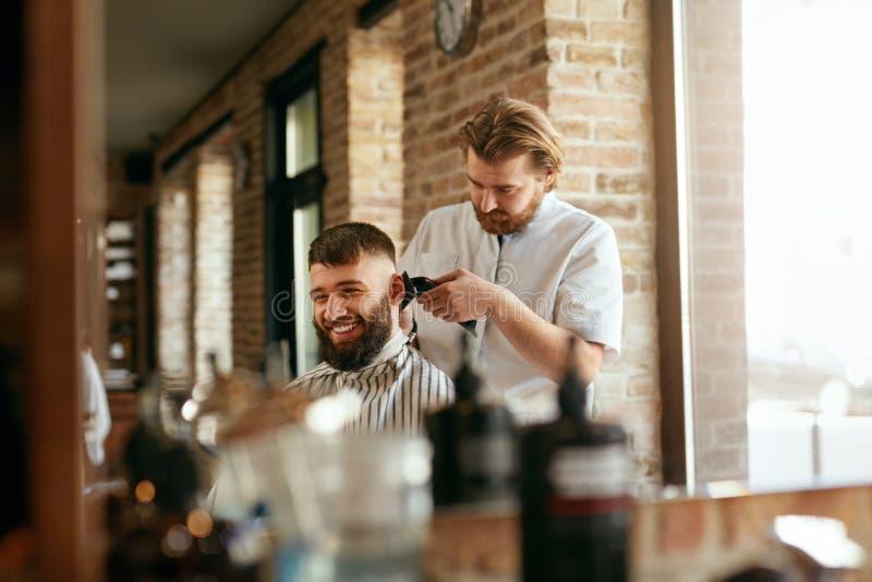 Barberaren shoppar Man som får frisyr i hårsalong royaltyfri foto