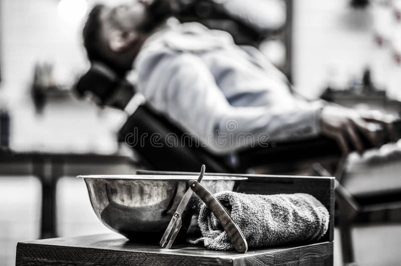 Barberaren shoppar, rakkniven Rak rakkniv för tappning Skönhetkvinna med långt sunt och skinande slätt svart hår Rak rakkniv för  royaltyfri bild