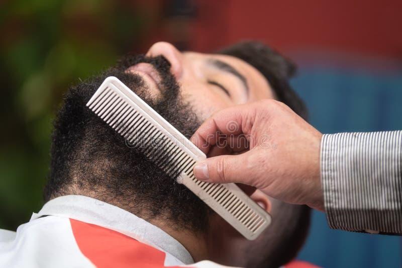 Barberaren som gör skägghaitstyle som använder hårkammen på barberaren, shoppar arkivbild